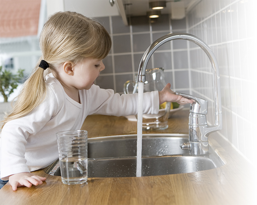 A girl turning on the water faucet.
